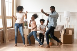 Happy african american parents and cute children dancing among boxes celebrating moving day relocation renovation, active carefree funny mixed race family mom dad having fun with kids in new house