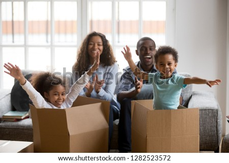 Happy african american parents and kids playing in boxes enjoy relocation into new home, excited mixed race children having fun help mom dad unpack in living room, black family on moving day portrait