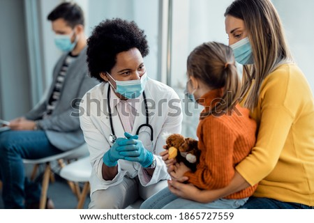 Happy African American pediatrician with face mask talking to mother and daughter in a waiting room at the hospital. Сток-фото ©