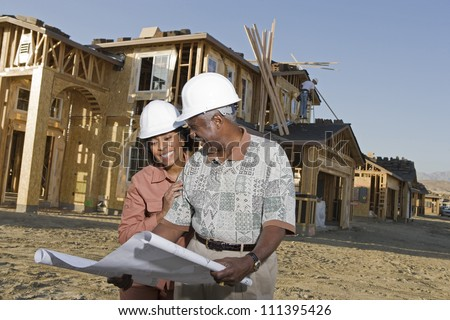 Happy African American senior couple holding blueprint in front of house under construction