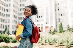 Happy African American Student Girl Posing With Backpack Holding Books Smiling Looking Aside Standing Near University Building Outdoor. Modern Education And Studentship Lifestyle