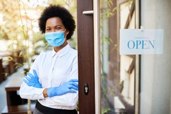 Happy African American waitress standing with arms crossed next to open sign at cafe and wearing protective face mask and gloves due to coronavirus epidemic.