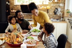 Happy African American woman having Thanksgiving lunch with her family and serving salad at dining table.