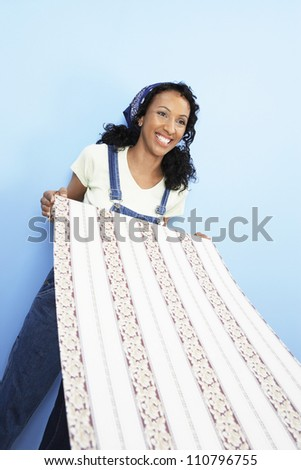 Happy African American woman holding wallpaper
