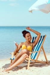 happy african american woman laying on deck chair and listening music in earphones with smartphone under beach umbrella in front of sea