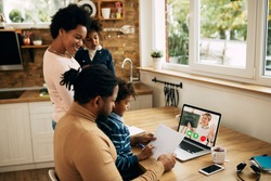 Happy African American woman reminding her husband to finish with work on laptop so that kids could follow online classes at home.