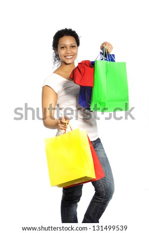Happy African American woman shopper returning from a spending spree carrying handfuls of colourful shopping bags with her purchases