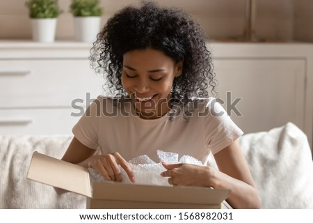 Happy african American woman sit on couch unpacking cardboard packaged with online order, excited biracial female feel overjoyed unwrap open box shopping on internet, good delivery service concept