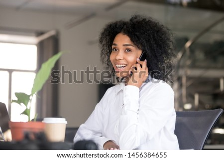 Happy African American woman take break from work talking over phone with friend, smiling female black employee have cell conversation in office, consulting client on cellphone. Technology concept