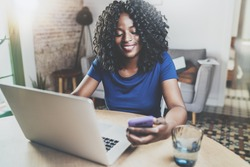 Happy african american woman using laptop and smartphone while sitting at wooden table in the living room.Horizontal.Blurred background