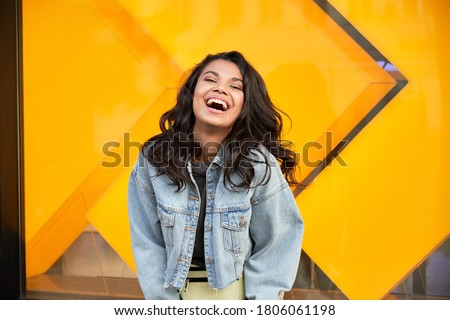 Happy African American woman wearing denim jacket laughing looking at camera standing near city street building. Smiling positive mixed race generation z hipster lady posing outdoor. Stok fotoğraf ©
