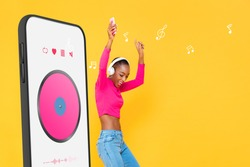 Happy African American woman wearing headphones listening to streaming music from smartphone application and dancing on colorful yellow isolated studio background
