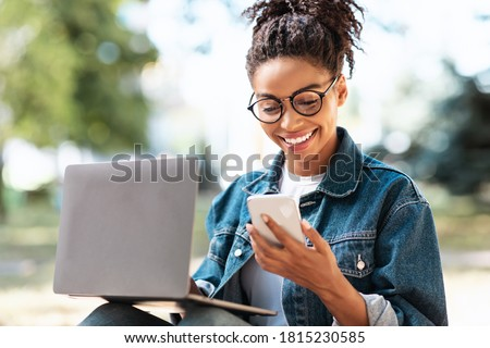 Happy African American Woman With Cellphone Texting Working On Laptop Sitting Outside. Good News Concept Stock photo ©