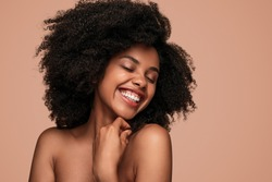Happy African American woman with curly hair closing eyes and cheerfully smiling while enjoying clean skin after spa session against brown background