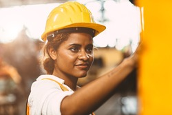 happy African American woman worker with safety suit helmet enjoy smiling working as labor in heavy industry factory with steel machine operator for good welfare.