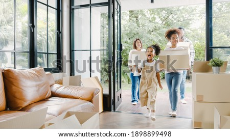 Happy African American young family bought new house. Mom, Dad, and child smiling happy hold cardboard boxes for move object walking into big modern home. New real estate dwelling, loan and mortgage. Stock foto ©