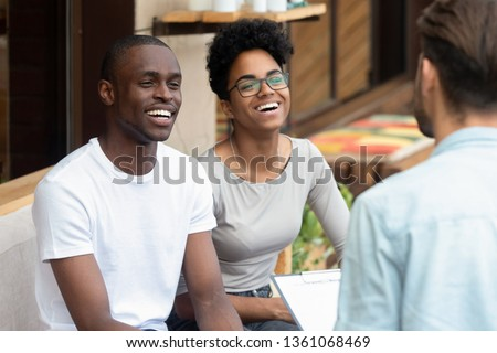 Happy african american young family couple listen to counselor psychologist salesman realtor consult black clients talk to patients customers holding clipboard at meeting, marriage therapy counseling