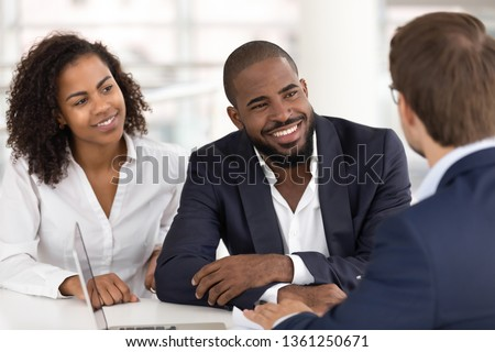 Happy african american young family couple listen to realtor insurer salesman consulting black clients at meeting, bank manager agent talking to customers explaining insurance loan mortgage deal