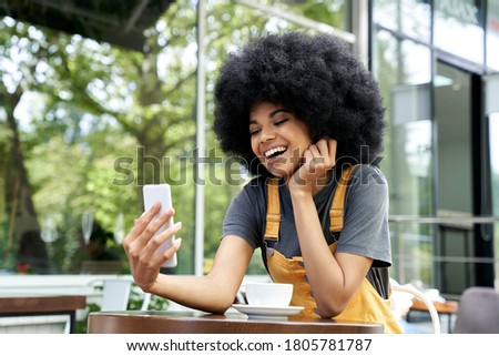 Happy African American young hipster gen z woman with Afro hair holding smart phone making video call, shooting social media blog talking with friend, watching video sitting at outdoor cafe table.