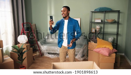 Happy African American young smiling man standing in newly rented or bought home video chatting on smartphone with friends showing new apartment on video call. Unpacking boxes. Move in concept Stock foto ©