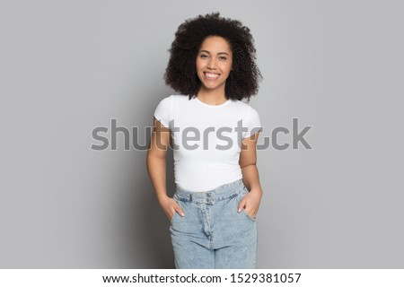 Happy african American young woman in casual clothes isolated on grey studio background posing, smiling mixed race ethnicity millennial girl model or actress look at camera hold hands in jeans