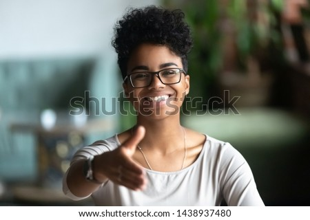 Happy african American young woman in glasses stretch hand for handshake greeting introducing to someone, smiling black biracial millennial female hr agent in spectacles get acquainted at meeting