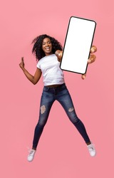 Happy african american young woman showing empty smartphone screen while jumping up over pink studio background, collage, full size photo. Excited black lady recommending nice mobile application