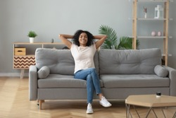 Happy african American young woman sit relax on cozy couch hands over head happy to move to new apartment, smiling black millennial girl rest on comfortable sofa in living room dreaming