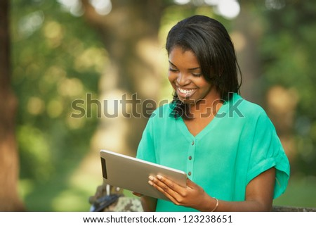 Happy African American young woman using tablet computer