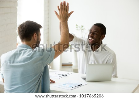 Happy african and caucasian businessmen giving high five in office, diverse motivated colleagues partners team celebrating good work result or business success, showing unity help support in teamwork