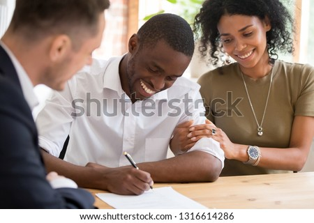 Happy african black family couple customers renters tenants sign mortgage loan investment agreement or rental insurance contract meeting realtor lender landlord making real estate sale purchase deal