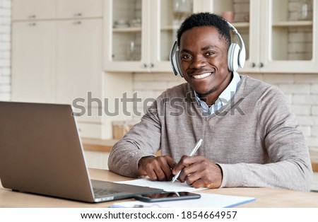 Happy african business man, black male student wearing headphones elearning on laptop sitting at kitchen table working from home office, learning online, studying remote course looking at camera.