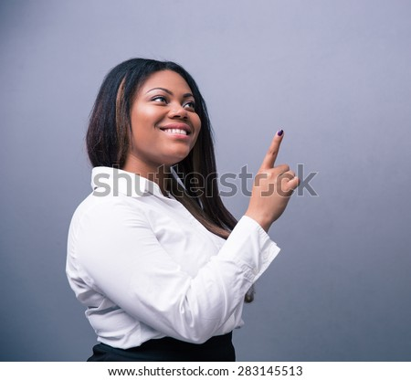 Happy african businesswoman pointing finger up over gray background #283145513