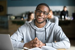 Happy african casual man in glasses sits at cafe table looking at camera, cheerful black student posing studying with book in coffee house, smiling businessman works on laptop in cafeteria, portrait