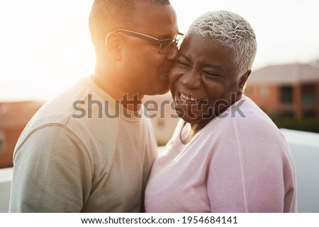 Happy african couple having tender moment outdoors at summer sunset - Focus on woman face