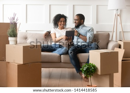 Happy african couple husband and wife choose house removal service or search renovating ideas sit on sofa with boxes, smiling black renters owners tenants use digital tablet on moving day in new home