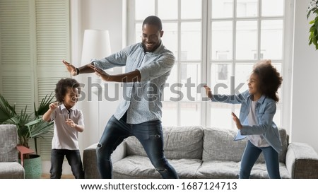 Happy African ethnicity father have fun teaches little preschool kids to dance in modern living room at home. Dad with son and daughter engaged in funny activity enjoy leisure carefree weekend concept