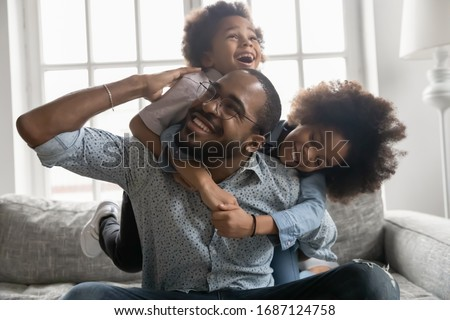 Happy African family at home, cute son and daughter hanging on daddy back, father fool around with little son and daughter piggy back siblings enjoy active time together seated on sofa in living room