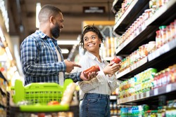 Happy African Family Couple Buying Food In Supermarket, Choosing Products Walking With Cart Along Aisles And Full Shelves Purchasing Groceries Together. Black Spouses Purchasing Essentials Together