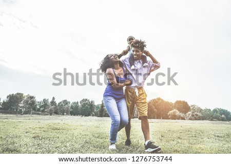 Happy african family having fun outdoor during sunny day in public park - Dad, mum and daughter enjoying tender moments together - Love and parenthood concept - Main focus on woman face