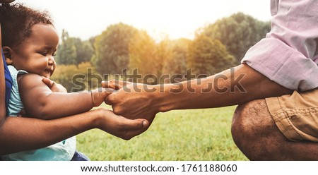 Happy African family having fun together in public park - Black father and mother holding hand with their daughter - people and parent unity concept Stock photo ©