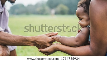 Happy african family holdings hands together outdoor during mother day - Mom, father and daughter having tender moments in nature green park - Love and unity concept