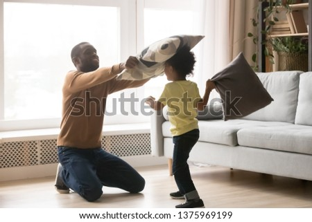 Happy african family playing together in modern warm house heated floor, father and little preschool son holding cushions fighting with pillows, active people having fun, free weekend at home concept