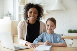 Happy African female tutor and little learner schoolgirl portrait. Multi-racial family sit in kitchen laptop and workbooks lie on table. Successful homeschooling, clever kid girl study at home concept