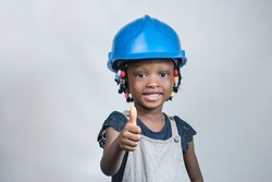 Happy African girl wearing blue helmet or hard hat and doing thumbs up gesture as she imitate successful engineers, architects, and other professional specialists in construction industries