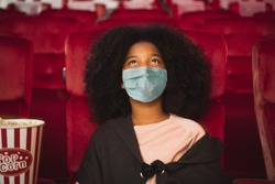 Happy african kid wearing protective face mask and watching movie in theater/theatre cinema protect infection from coronavirus covid-19, social distancing in theater concept