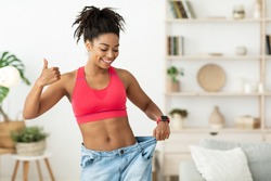 Happy African Lady Showing Result Of Successful Weight Loss Gesturing Thumbs-Up, Wearing Old Oversize Jeans Standing At Home. Slimming Motivation And Dieting Concept. Blank Space For Text