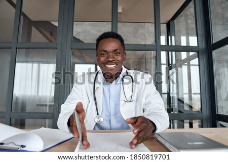 Happy african male doctor talking to camera during telehealth mobile consultation. Black physician consulting patient in virtual telemedicine phone app chat. Tele medicine videocall visit, headshot.