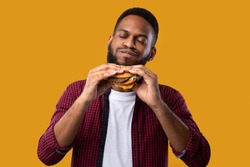 Happy African Man Eating Burger Posing Standing Over Yellow Studio Background. Black Guy Tasting Cheeseburger Enjoying Unhealthy Junk Food. Nutrition And Overeating Habit