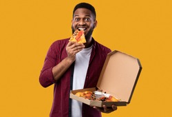 Happy African Man Eating Pizza Smiling To Camera Standing Over Yellow Studio Background. Junk Food Eater Enjoying Unhealthy Pizza. Nutrition And Cheat Meal, Fastfood Overeating Habit
